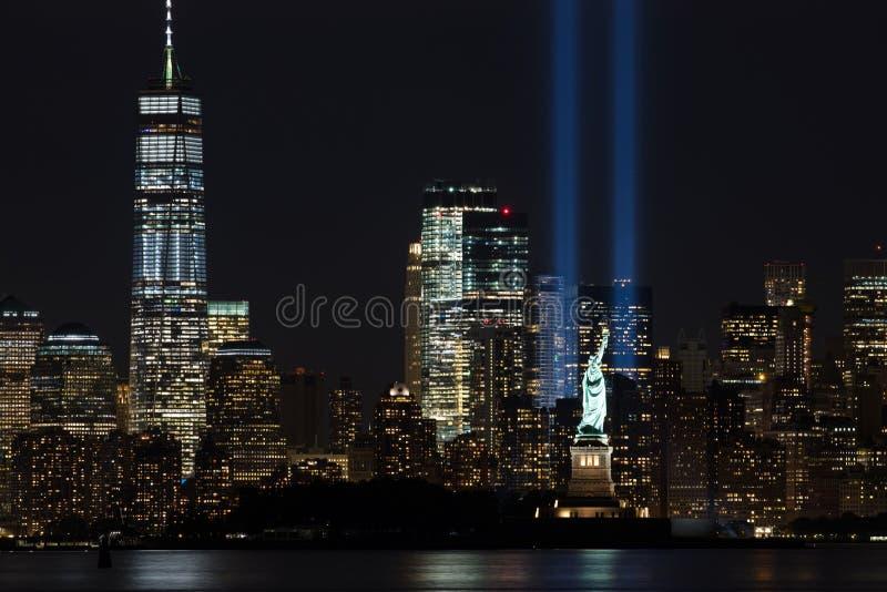 Haces de 9/11 monumento con la estatua de la libertad y del Lower Manhattan imagenes de archivo