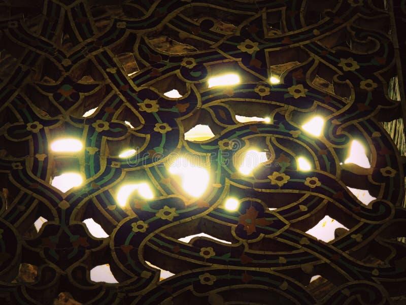 Haces luminosos de Sun a través de mosaicos florales de la ventana en la mezquita de Isfahán fotos de archivo libres de regalías