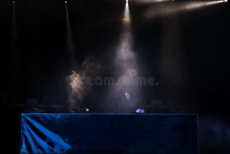 Haces luminosos en la etapa, el humo y la mujer joven DJ jugando música en el festival de la noche de verano fotografía de archivo