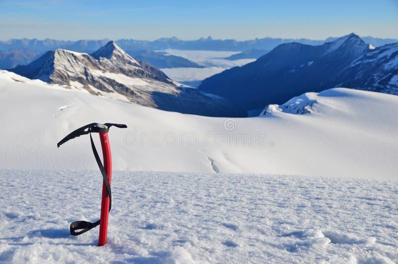 Hacha de hielo en la nieve foto de archivo
