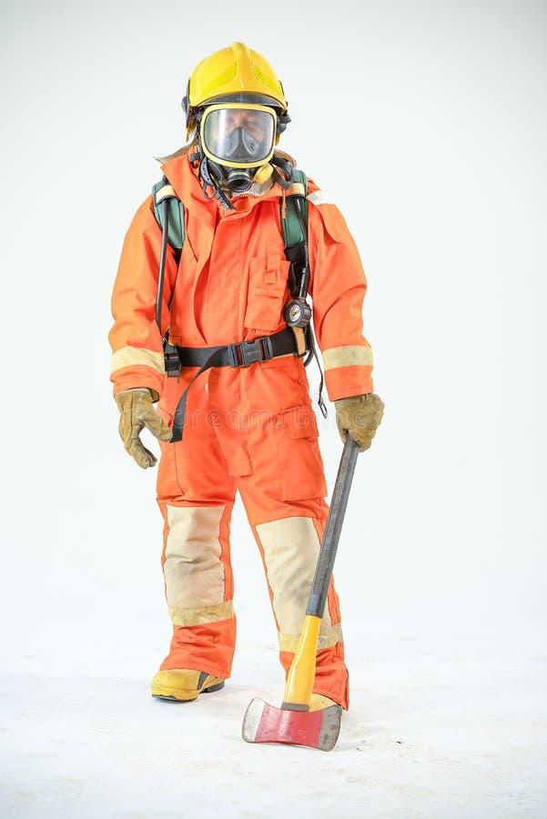Hacha de la tenencia del bombero con el uniforme anaranjado en el fondo blanco fotos de archivo libres de regalías