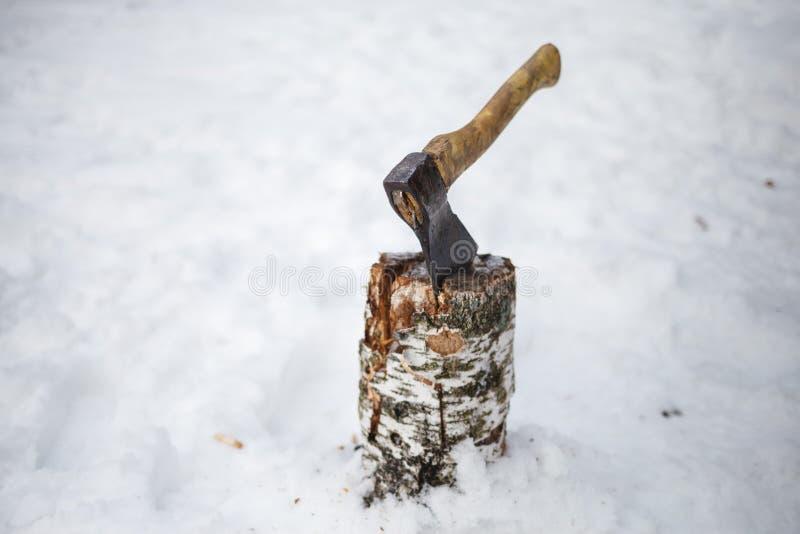 Hacha en una cubierta en la nieve en invierno foto de archivo