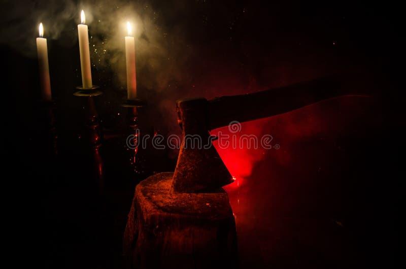 Hacha vieja atada al tronco de árbol en fondo de niebla rojo del horror Tema asustadizo de Halloween con el arma maniaca del ases foto de archivo