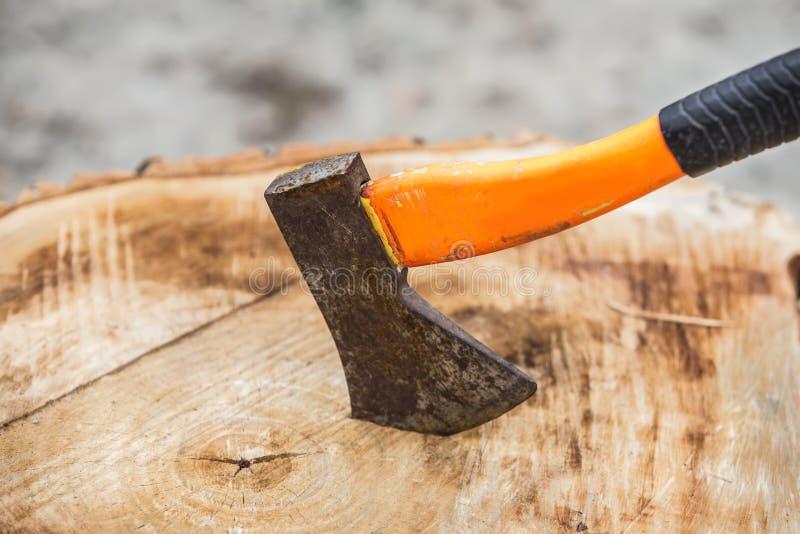 Hache dans un grand tronçon en bois photographie stock libre de droits