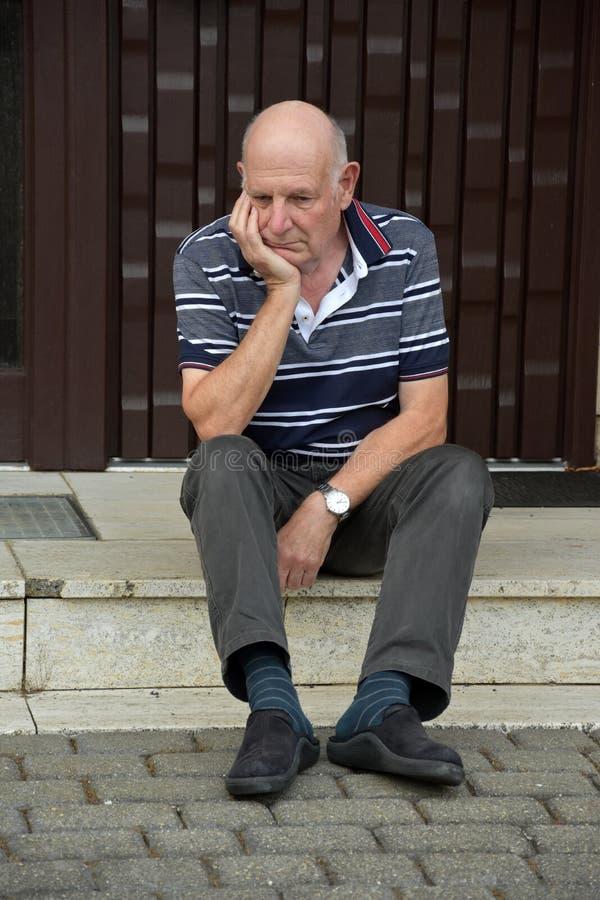 Hacia fuera hombre mayor bloqueado que se sienta delante de su casa foto de archivo libre de regalías