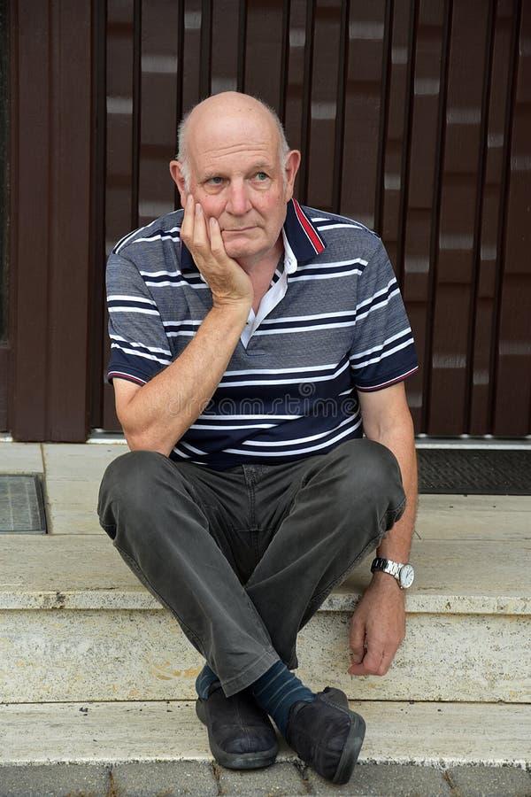 Hacia fuera hombre mayor bloqueado que se sienta delante de su casa imagen de archivo