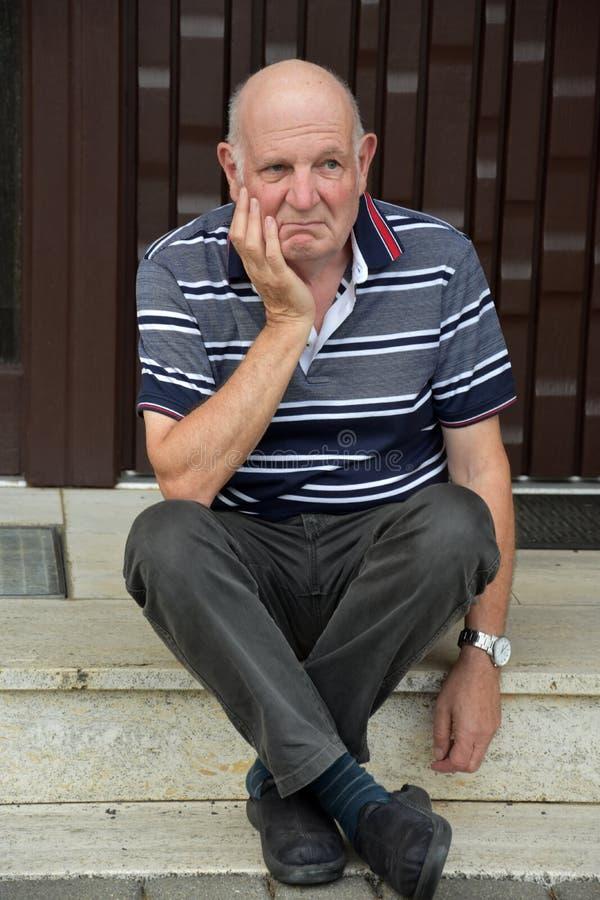 Hacia fuera hombre mayor bloqueado que se sienta delante de su casa imagenes de archivo