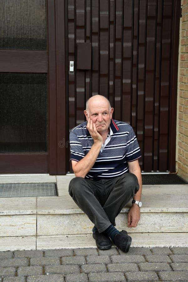 Hacia fuera hombre mayor bloqueado que se sienta delante de su casa foto de archivo