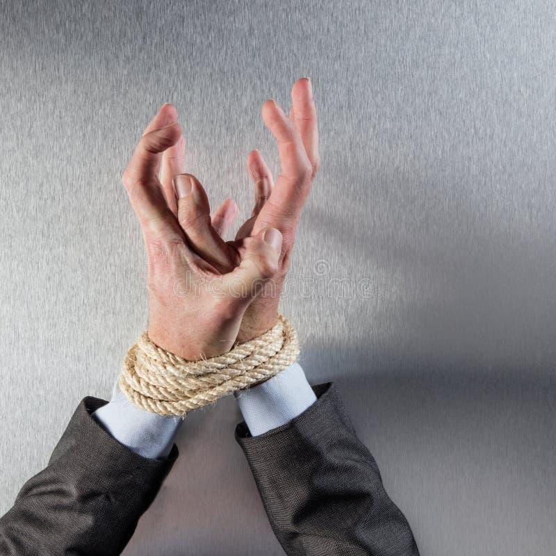 Hacia fuera subrayadas manos del hombre de negocios atadas con la cuerda que busca para la ayuda foto de archivo