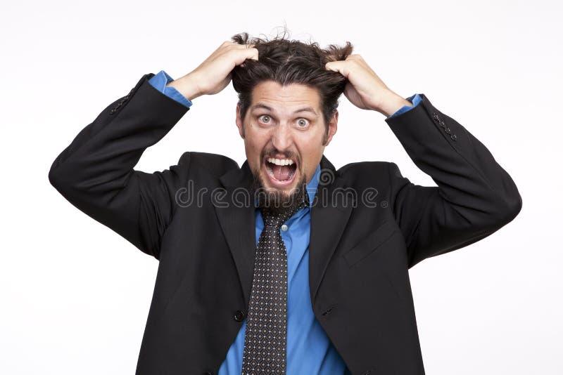Hacia fuera subrayado hombre de negocios que tira de su pelo y que grita imagenes de archivo