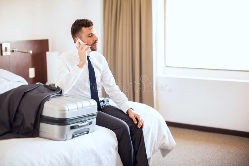 Haciendo algunas llamadas antes de salir del hotel fotografía de archivo