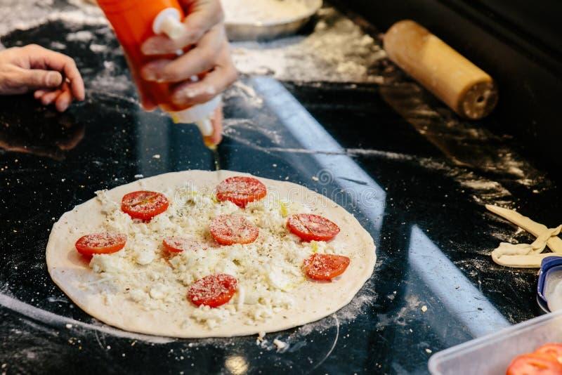 Haciendo a Caprese Bianca Pizza añadiendo el aceite de oliva en la pasta con el tomate, la mozzarella y el queso parmesano cortad fotografía de archivo libre de regalías