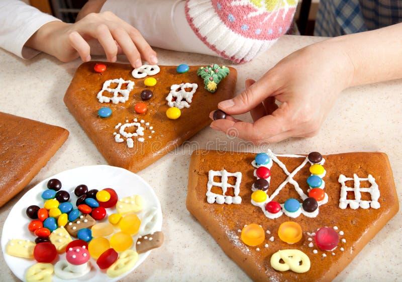 Haciendo la casa de pan de jengibre de la Navidad junto foto de archivo libre de regalías