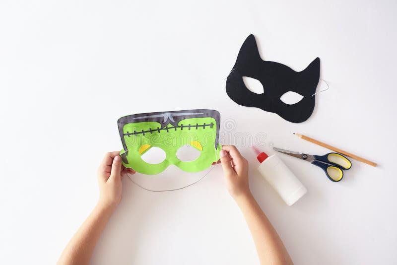 Haciendo las máscaras el ` de papel s del monstruo de Halloween del día de fiesta enmascare las manos del gato negro visión super foto de archivo