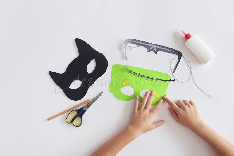 Haciendo las máscaras el ` de papel s del monstruo de Halloween del día de fiesta enmascare las manos del gato negro visión super imagen de archivo