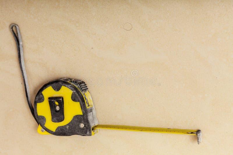 Haciendo a mano, objetos que se ocupan vanamente Cinta m?trica negra y amarilla imagen de archivo libre de regalías