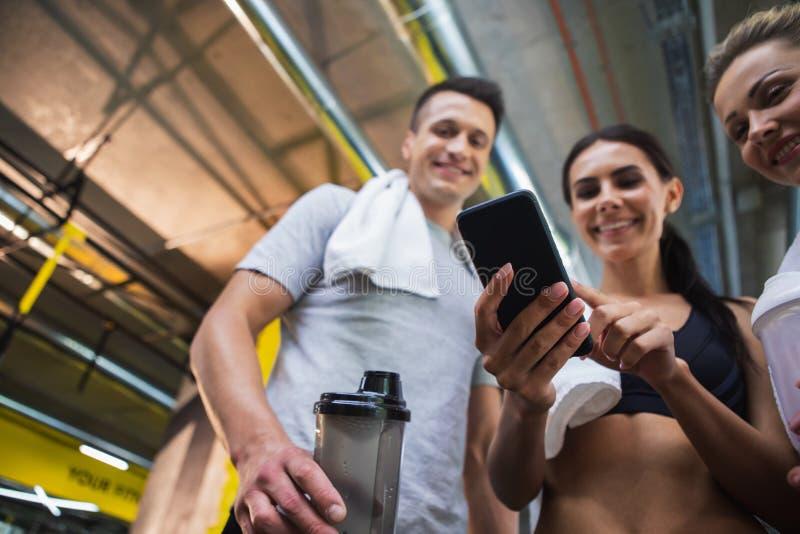 Haciendo muecas los amigos están pasando tiempo con smartphone durante entrenamiento imagen de archivo