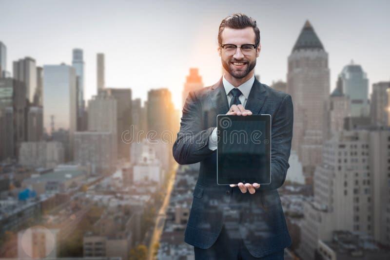 Haciendo negocio más fácil Retrato del hombre joven alegre en el traje que muestra la tableta digital y que sonríe mientras que s imagenes de archivo