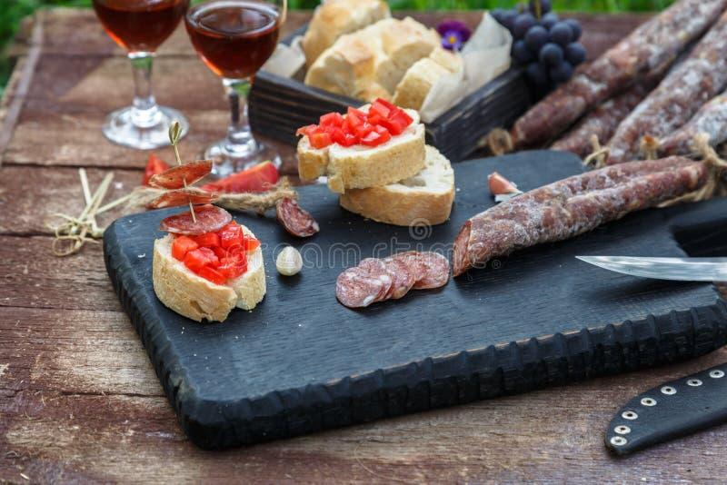 Haciendo pintxo con el tomate y las salchichas, los tapas, los canapes españoles van de fiesta el comida para comer con los dedos imágenes de archivo libres de regalías