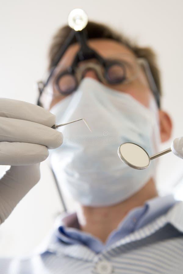 hacka för tandläkareholdingspegel royaltyfri foto