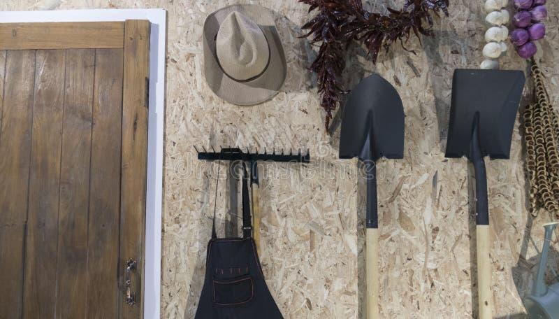 Hacka, skyffla, harvet och hatten bredvid trädörr arkivbilder