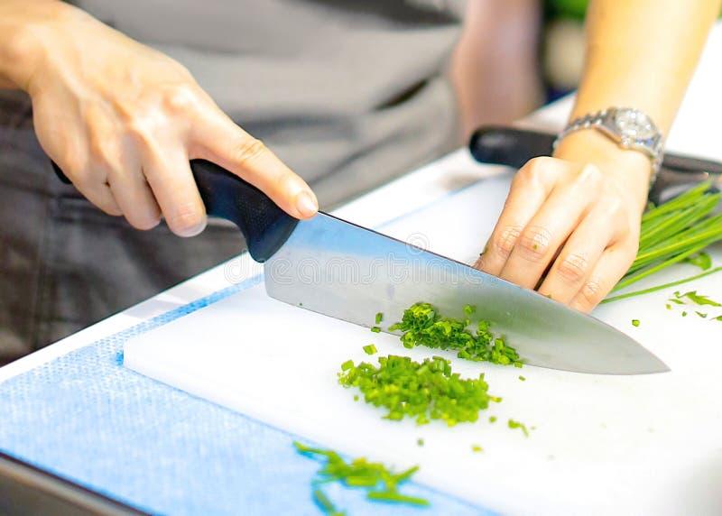 Hacken der Frühlingszwiebel, Chef, der Frischgemüse für das Kochen schneidet lizenzfreie stockbilder