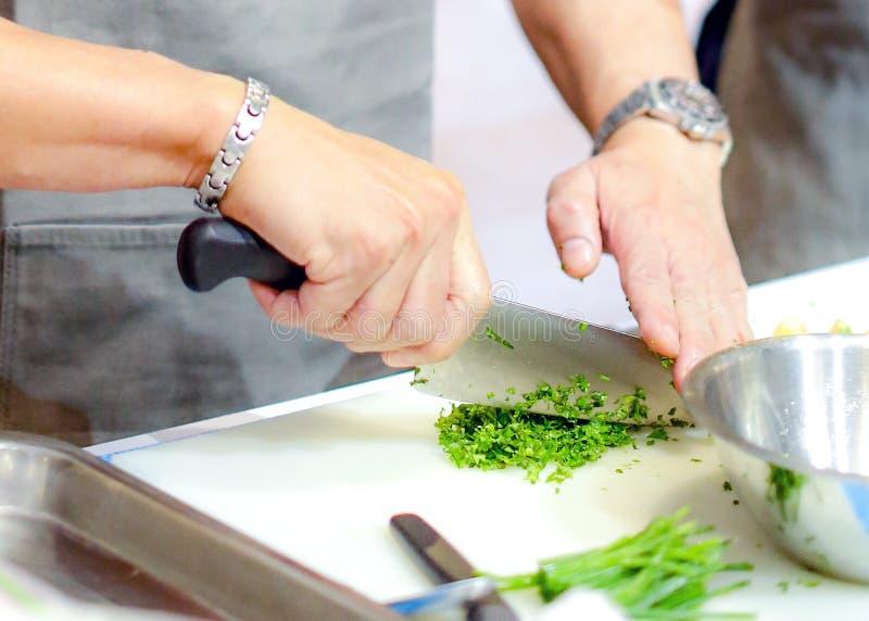 Hacken der Frühlingszwiebel, Chef, der Frischgemüse für das Kochen schneidet stockbilder