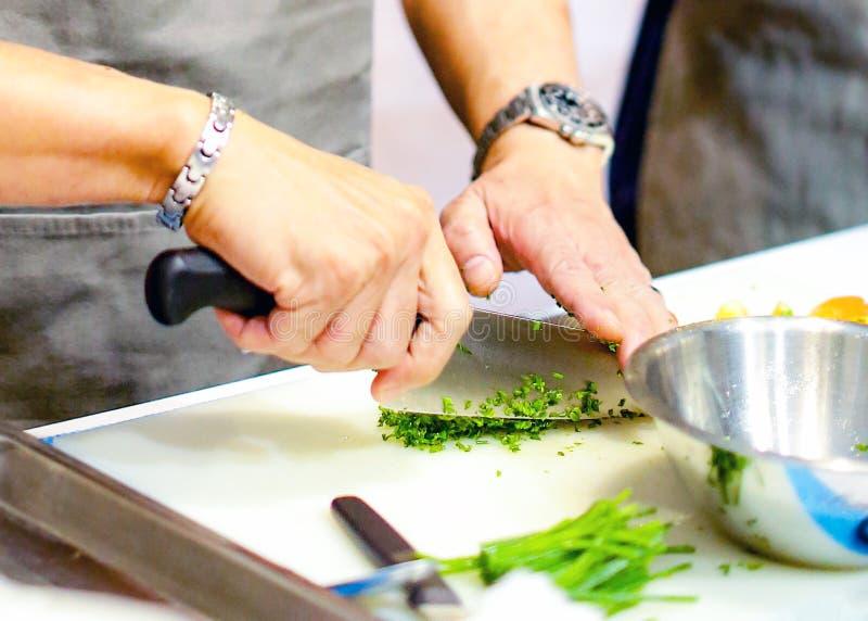 Hacken der Frühlingszwiebel, Chef, der Frischgemüse für das Kochen schneidet lizenzfreie stockfotografie