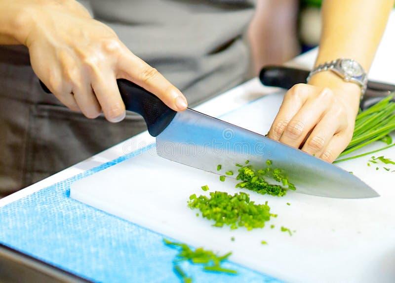 Hacken der Frühlingszwiebel, Chef, der Frischgemüse für das Kochen schneidet stockfoto