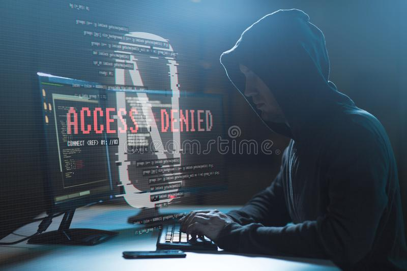 Hacker with access denied messages on computer. Cybercrime, hacking and technology concept - male hacker with access denied message on computer screen using royalty free stock photos