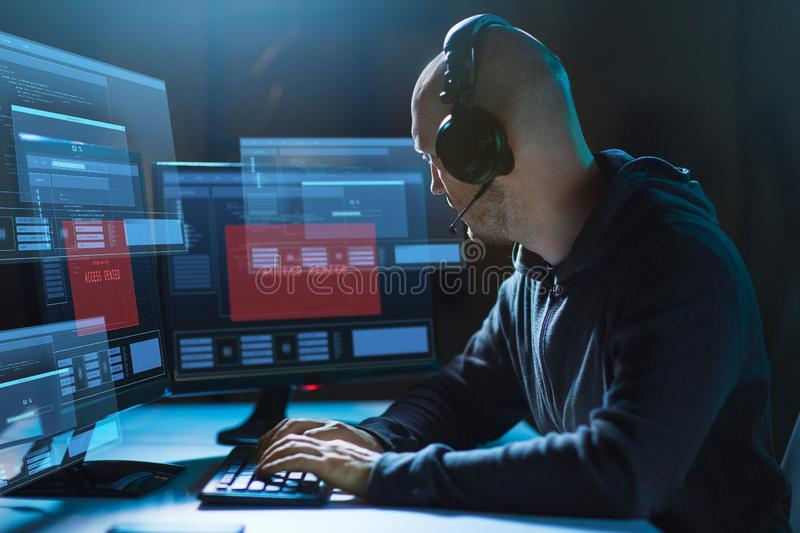 Hacker with access denied messages on computers. Cybercrime, hacking and technology concept - male hacker in headset with access denied messages on computer`s stock images