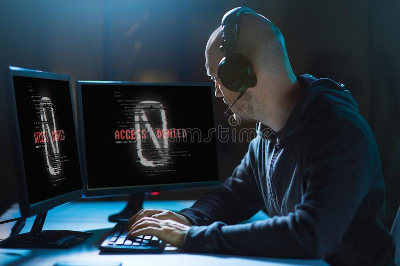 Hacker with access denied messages on computers. Cybercrime, hacking and technology concept - male hacker in headset with access denied messages on computer`s royalty free stock image