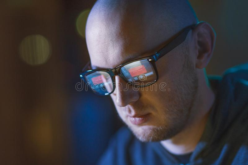 Hacker with access denied reflecting in glasses. Cybercrime, hacking and people concept - close up of hacker with access denied message reflecting in glasses royalty free stock photos
