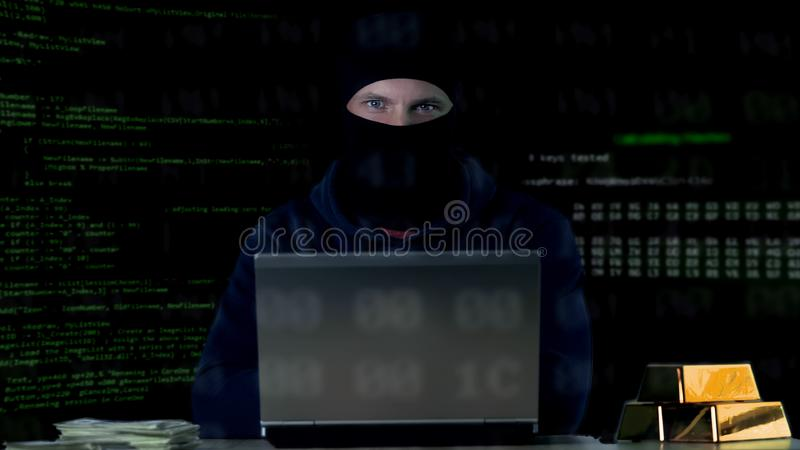 Hacker in balaclava committing cyber crime on laptop, numbers codes background stock images