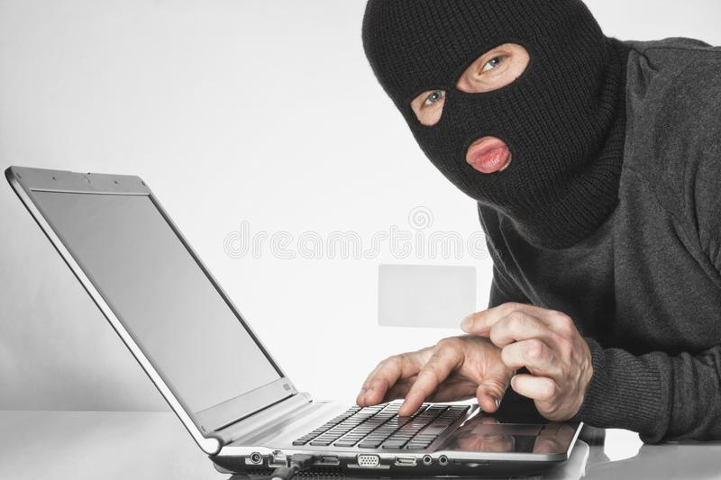 Hacker in balaclava holding a card in left hand and typing something with right hand on laptop keyboard royalty free stock images