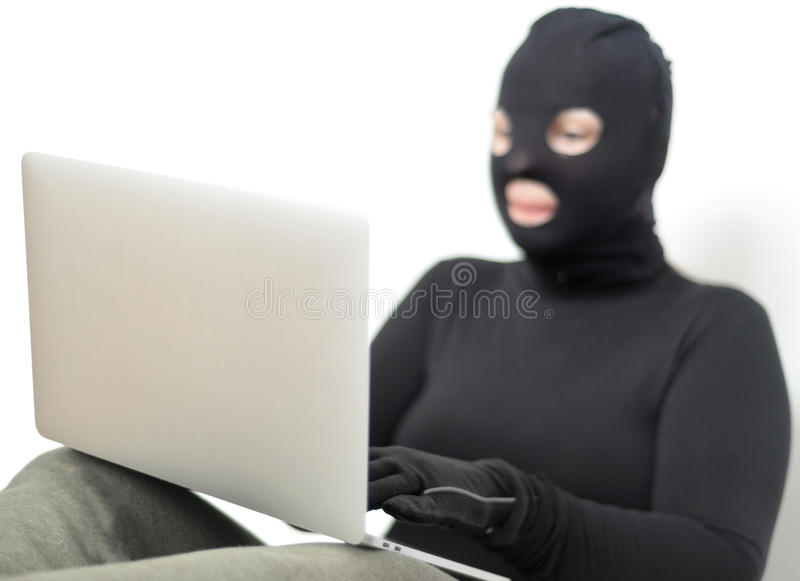 Hacker. In balaclava with laptop, crime royalty free stock images