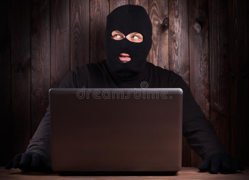 Hacker in a balaclava. Standing in the darkness furtively stealing data off a laptop computer on wooden background stock photography