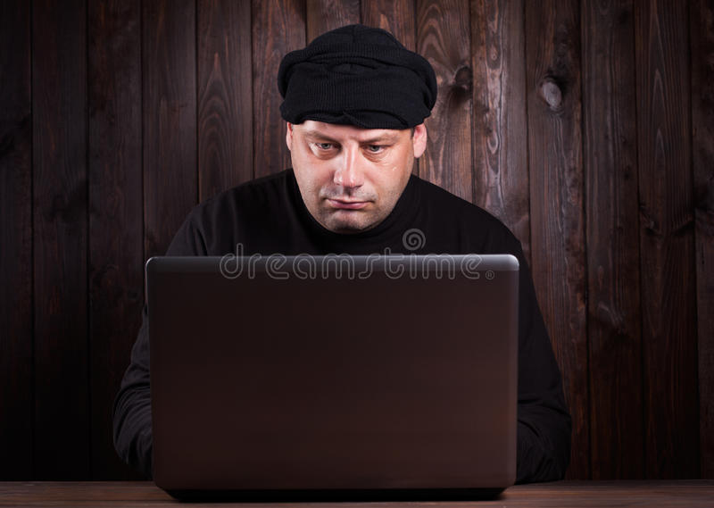 Hacker in a balaclava. Standing in the darkness furtively stealing data off a laptop computer on wooden background royalty free stock images