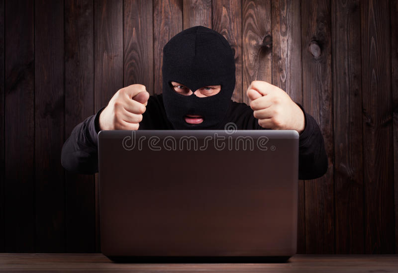Hacker in a balaclava. Standing in the darkness furtively stealing data off a laptop computer on wooden background stock photo