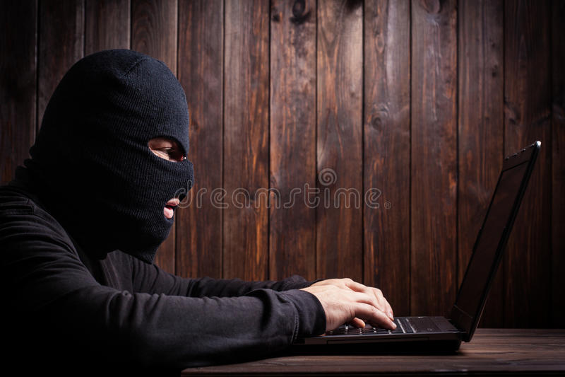 Hacker in a balaclava. Standing in the darkness furtively stealing data off a laptop computer on wooden background stock images