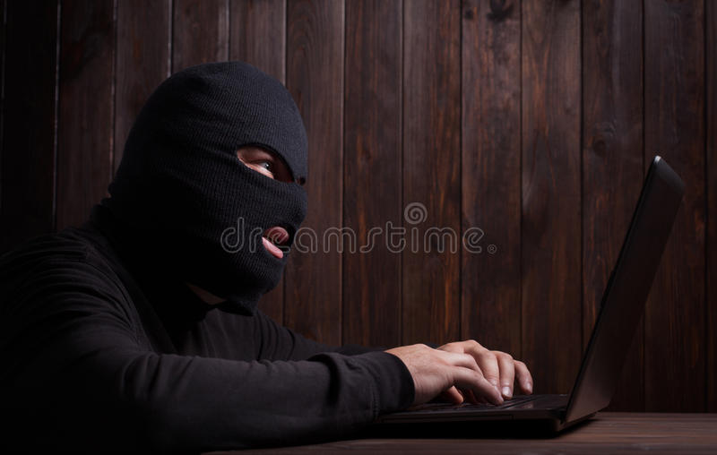 Hacker in a balaclava. Standing in the darkness furtively stealing data off a laptop computer on wooden background royalty free stock photo