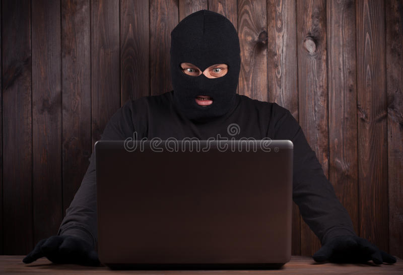 Hacker. In a balaclava standing in the darkness furtively stealing data off a laptop computer on wooden background royalty free stock images