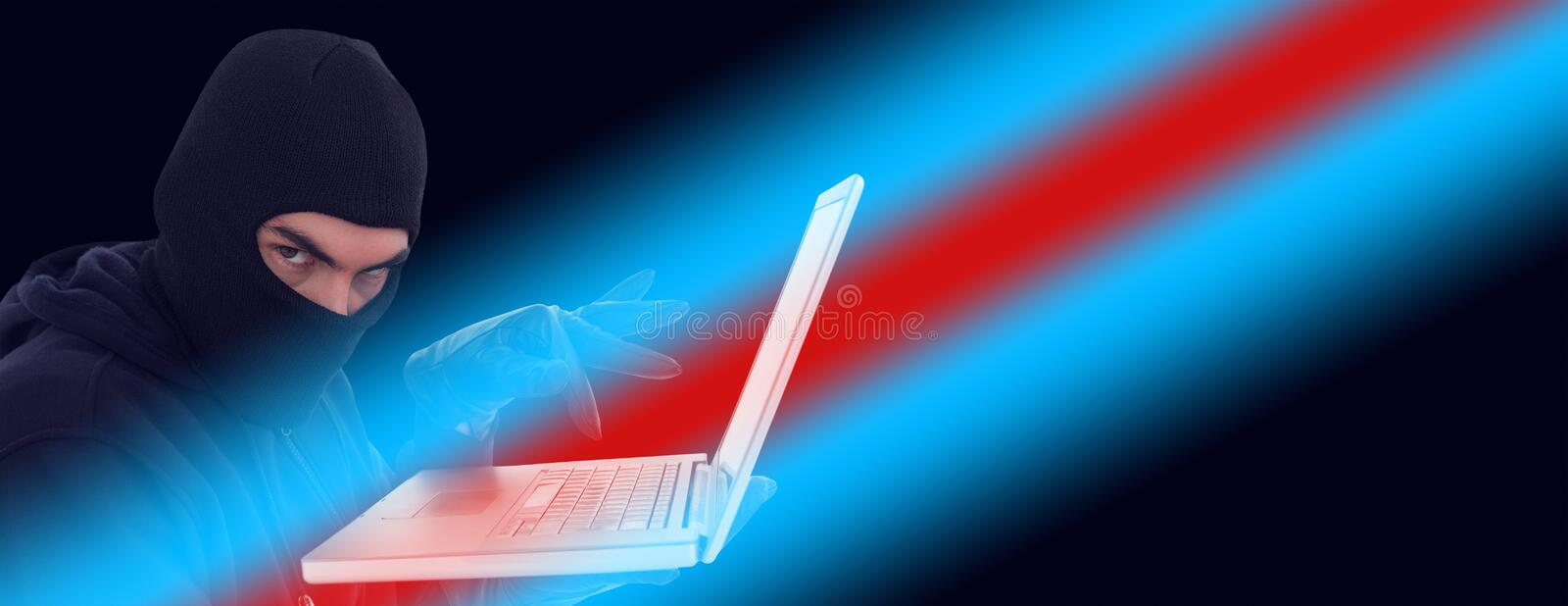 Hacker in balaclava standing and typing on laptop royalty free stock image