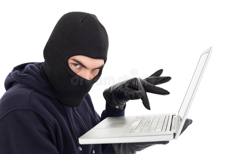 Hacker in balaclava standing and typing on laptop stock image