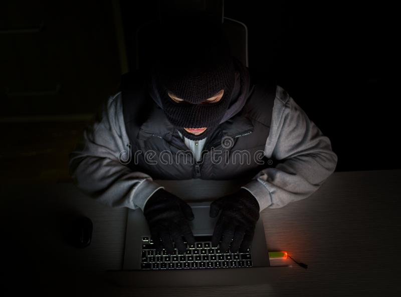 Hacker with balaclava typing on laptop stock images