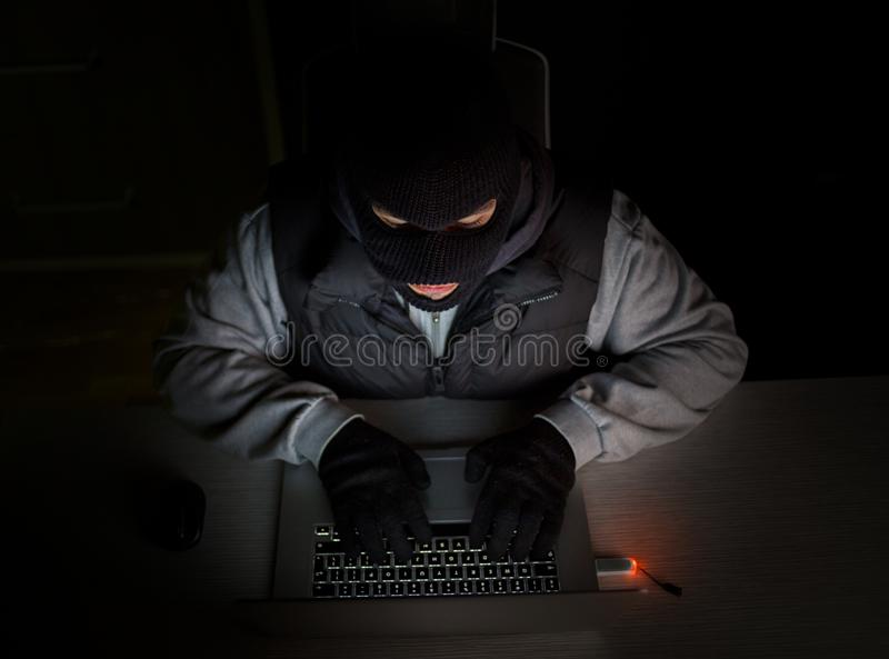 Hacker with balaclava typing on laptop royalty free stock photos