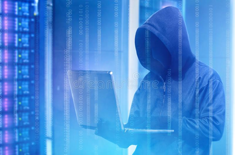 Hacker in black hoodie holding laptop with binary code on virtual screen. With modern storage of server in the data center on the background royalty free stock image