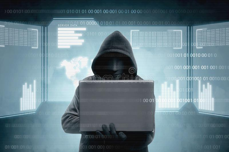 Hacker in black hoodie holding laptop and virtual screen display the server data, binary code, bar graph and world map. Over dark background royalty free stock image