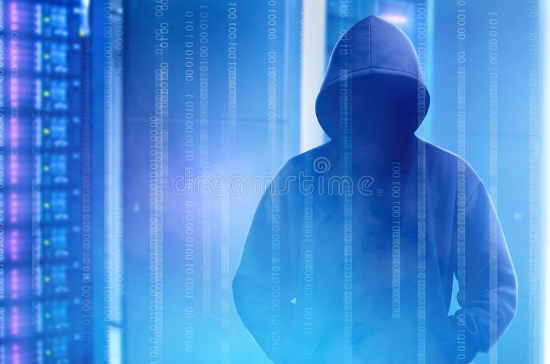Hacker in black hoodie standing with binary code on virtual screen. With modern storage of server in the data center on the background royalty free stock image