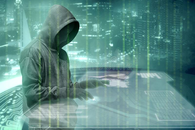 Hacker in black hoodie touching virtual screen on the table with server data, binary code, bar graph and world map. With green background royalty free stock photography